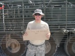 "Jeremy holding a sign that says ""I love you and miss you!"" and standing in front of a Stryker"