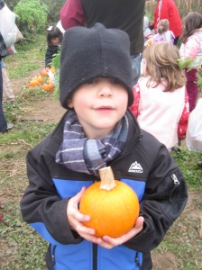 Did I mention it was pretty cold this morning? Here's Coop, proud of his pumpkin and bundled up with Daddy's skull cap on!